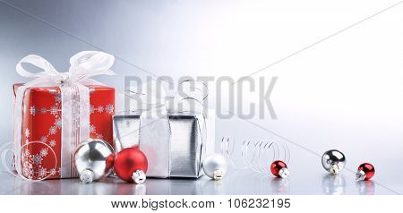 Christmas gift box with decoration on shiny background
