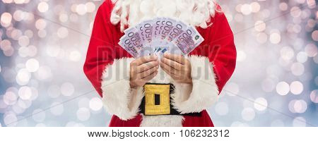 christmas, holidays, winning, currency and people concept - close up of santa claus hands holding euro money over lights background