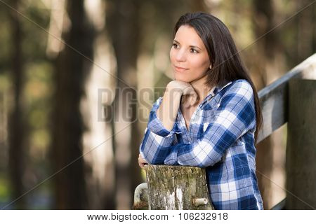 Beautiful brunette woman leaning on fence