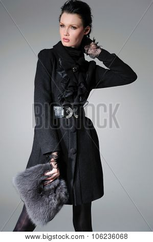 fashion model in autumn/winter clothes with hat holding handbag posing