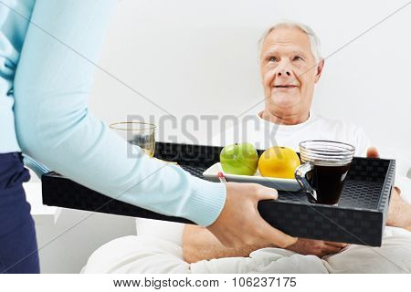Old man eating breakfast in bed at home