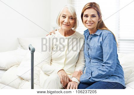 Happy senior woman with adult daughter sitting at home on a bed