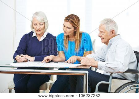 Woman consulting senior couple in nursing home