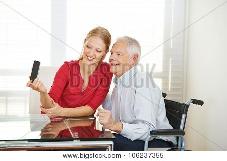 Young woman taking selfie with grandfather in a nursing home