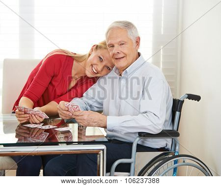Happy granddaughter playing cards with grandfather in wheelchair