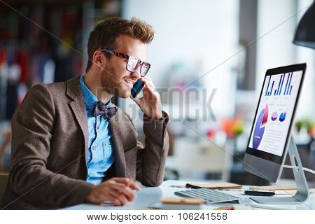 Busy employee speaking on the phone while looking at computer screen