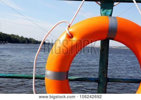 A life buoy hangs on the pier's handrail, close up