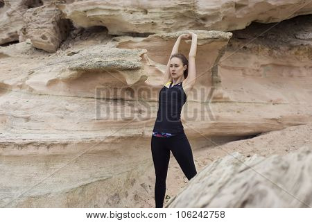 Attractive sportive woman with beautiful figure doing stretching exercise for arms before her jog