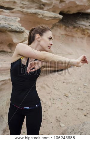 Fit caucasian woman with perfect body working out in stone rock mountains