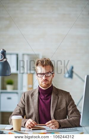 Young businessman looking at camera with suspicious expression