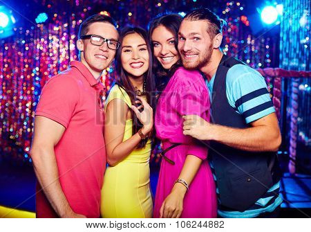 Friendly clubbers looking at camera at party