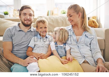 Happy family in casualwear sitting on sofa at home