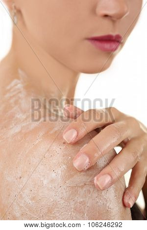 Woman using body scrub isolated on white