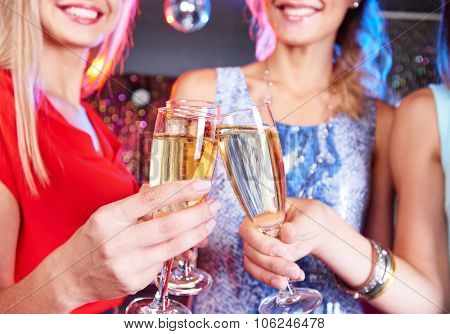 Happy friends clinking with flutes of champagne