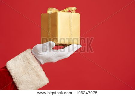 Gloved Santa hand with golden giftbox