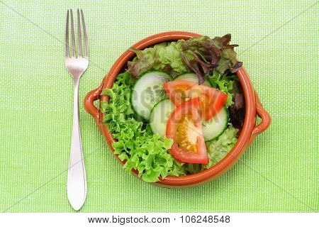 Green salad consisting of lettuce, tomatoes and cucumber in clay bowl on place mat