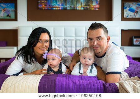 Happy family portrair. Parents with baby boy and girl twins.