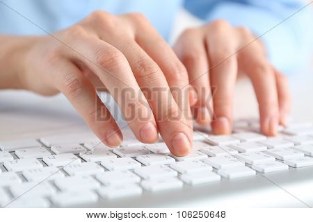 Female hands typing on keyboard close up