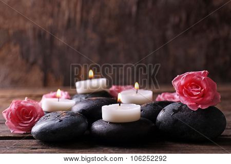 Tenderness relaxing composition with pebbles, roses and candles on wooden background