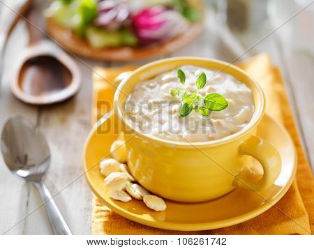 new england clam chowder with oyster crackers in yellow bowl horizontal shot
