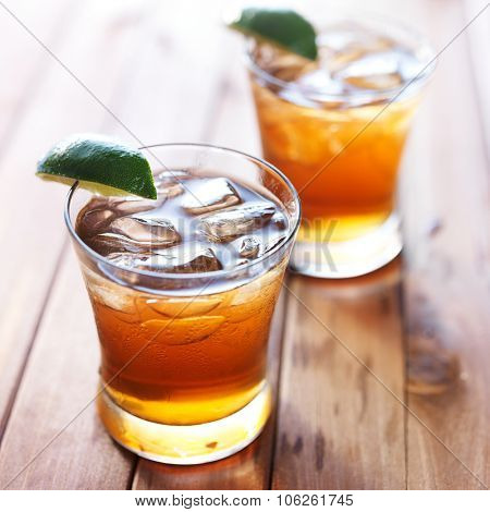 iced tea in short glass with lime wedges