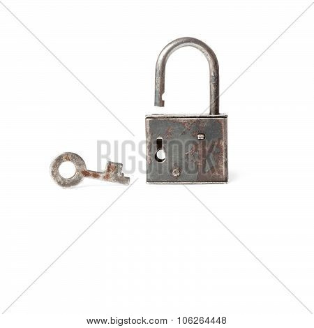 Textured ancient opened padlock with key on white background.
