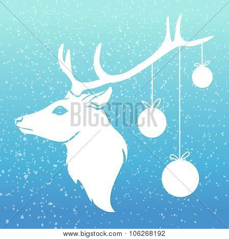Christmas deer with x-mas balls on his horn with snow on blue background