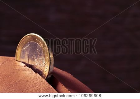 closeup of a coin of one euro in the hole of an earthenware piggy bank