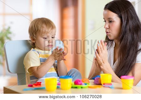 child boy and woman playing colorful clay toy at nursery or kindergarten