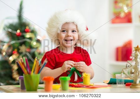 child girl making by hands christmas decorations