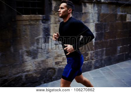 Portrait of a strong fit men dressed in sportswear jogging on the street in summer day