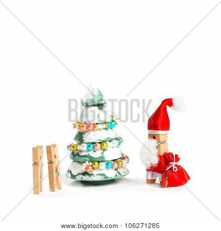 Wooden clothespin Santa Claus with bag gift, kids and decorated christmas tree.