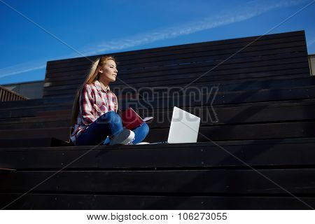 Young pretty women working on net-book while relaxing in the fresh air