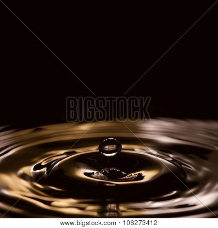 Liquid drops. splashing. gold, black, white waves. Black background.