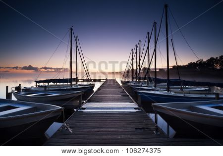 Pier And Yacht On Lake At Sunrise