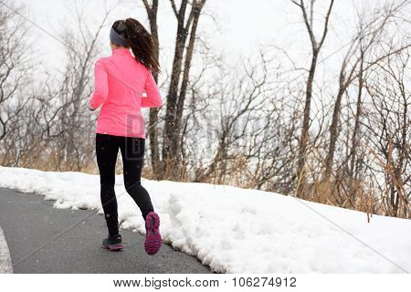 Winter jogging in park - female runner from the back exercising her cardio wearing pink jacket, active leggings and running shoes on city path.