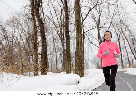 Winter cardio exercise - woman jogging doing her workout outside. Young adult running in outdoor park with snowy forest background wearing cold weather gear.