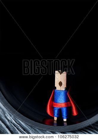 Abstract clothespin super hero in tube. Leadership concept man against black background. Blue suit and red cape. shallow dof. copy space