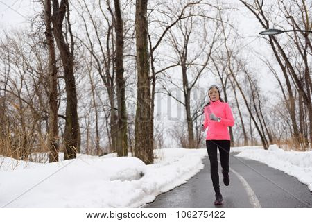Woman jogging in snowy city park - winter fitness. Female athlete exercising outside in cold weather on forest path wearing activewear. Windbreaker pink jacket, warm tights, running shoes.