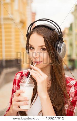 Pretty Casual Girl With Headphones Drinking Milkshake