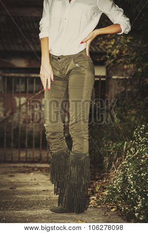 woman in white shirt,  green tight pants and tassel boots, stand in front old building, closeup