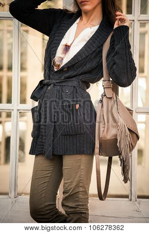 woman in worm dark wool sweater,  black leather high boots hold leather hand bag with tassels   stand in front glass door, closeup, outdoor shot