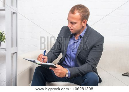 Handsome Businessman Sitting On Couch With Notebook At Home In The Living Room