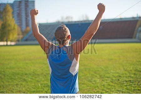 Athletic Man Is Happy And Rejoicing At The Stadium, Raised His Hands Up. Winner.