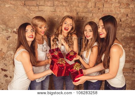 Cheerful Pretty Girls Giving Presents To Their Friend