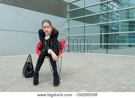 Young sad business woman sitting alone in modern background.