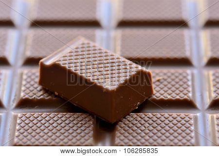 A piece of chocolate on chocolate background