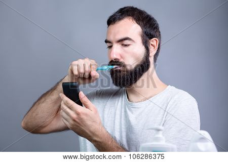 Man with Toothbrush and Smartphone