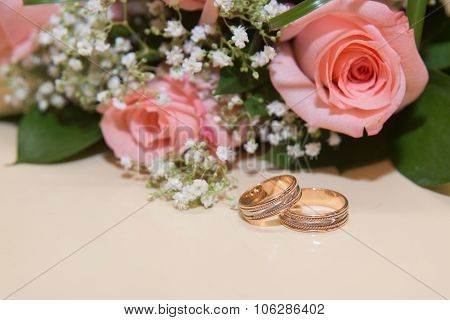 Two wedding rings lie the table.Beckett pink roses.
