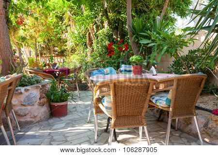 Tables with chairs at shaded cafe terrace in Crete